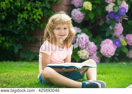 Outdoor Portrait Of A Cute Young Little Boy Reading A Book. Back To School. Kids Education. Beginnin