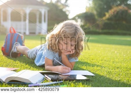 Beautiful Child Boy With Book Writing Notes In Copybook On Grass Background. Kids Reading Book In Pa