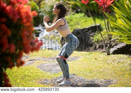 Young Woman Practicing Squats In Park. Fit Girl Exercising Outdoors On Summer Day. Female Fit Back A