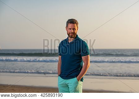 Portrait Of Man On Beach. Portrait Of Middle Aged Man With A Serious Expression And Ocean Backdrop S