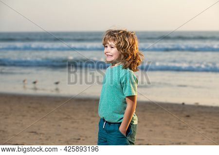 Child Boy In T-shirt With Hand In Pocket Walking On The Summer Beach.
