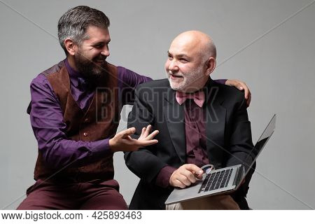 Adult Education. Businessmen Discussion With Laptops. Old Father And Young Man Looking At Laptop Scr