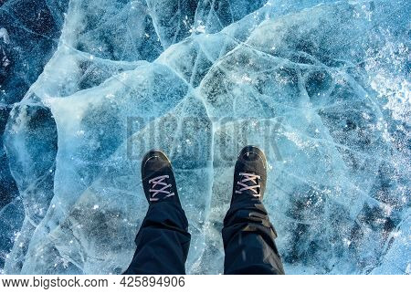 A Foot Of Tourist Standing On The Cracks Surface Of Frozen Lake Baikal In The Winter Season Of Siber