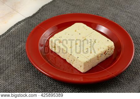 Block Of Tomato And Basil Feta Cheese On Red Plate On Gray Burlap Table Runner