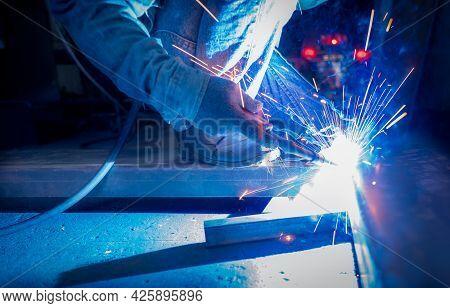 Welder Welding Metal With Argon Arc Welding Machine And Has Welding Sparks. A Man Wears Protective G
