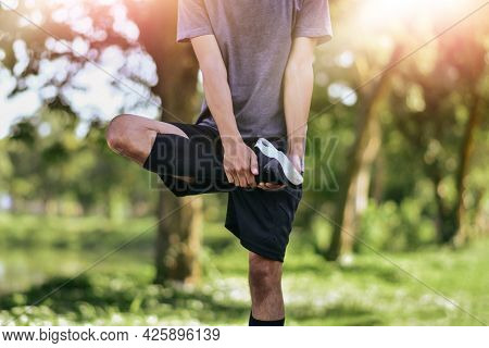 Man Stretching His Leg Muscles Before Exercising, Young Male Jogger Athlete Training