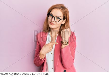 Young caucasian woman wearing business style and glasses in hurry pointing to watch time, impatience, looking at the camera with relaxed expression