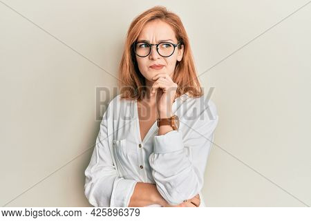 Young caucasian woman wearing casual clothes and glasses thinking concentrated about doubt with finger on chin and looking up wondering