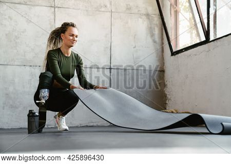 Young sportswoman with prosthesis unrolling fitness mat indoors