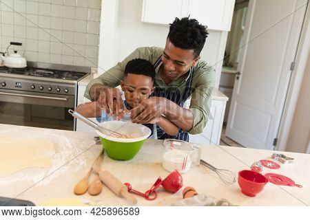 African american father and son baking in kitchen breaking eggs into mixing bowl. family enjoying quality free time together.