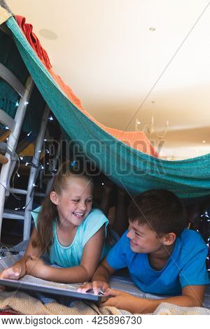 Caucasian brother and sister smiling, lying in blanket fort using tablet at home. childhood with technology, spending free time at home.