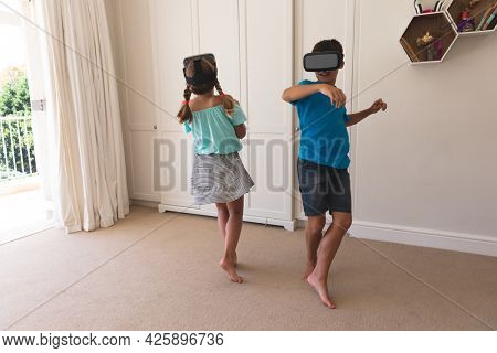 Caucasian boy and girl using vr headsets smiling at home. childhood with technology, spending free time at home.