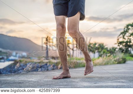 A Man Runner Is Engaged In Jogging On A Concrete Path Without Shoes, Without Sneakers, For Health