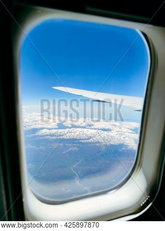 View Of The Snowy Peaks And Blue Sky From The Plane Window