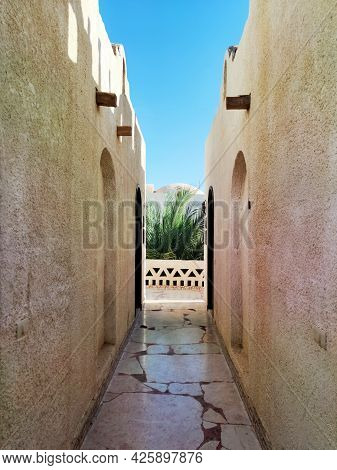 A Narrow Passageway Between Two African-style Buildings Against A Blue Sky.