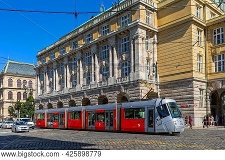 PRAGUE, CZECH REPUBLIC - SEPTEMBER 04, 2019: Modern tram on the cobblestone street in historic center of Prague - capital and largest city of Czechia, famous and popular tourist destination.