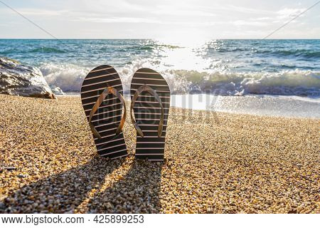 Flip-flops On Sea Beach Against Sunny Seascape. Flip Flops Slippers In Nautical Style In Small Stone