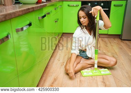 Smiling Woman Housewife With Mop Cleaning Floor In Kitchen. House Cleaning Routine. Caucasian Girl W