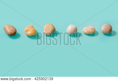 Small Stones Similar To Pebbles Lying On A Turquoise Background Horizontally. Horizontal Picture Wit