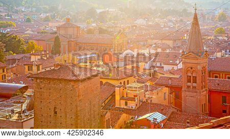 Red tiled roofs of Bologna city in sunlight at sunset, Italy. Italian cityscape