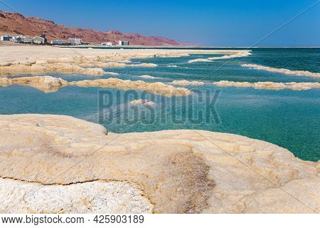 The evaporated salt forms bizarre patterns on the surface of the water. The Israeli coast of the Dead Sea. Windy spring day.