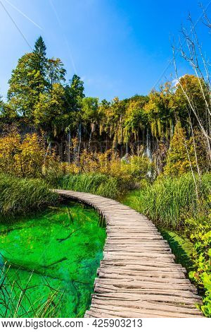 Plitvice Lakes Park in Croatia. Wooden footbridge over a picturesque shallow lake. Plitvice Lakes are beautiful karst lakes of turquoise color. Travel to Central Europe