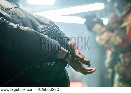 Captured criminal in cuffs bending forwards after committing crime
