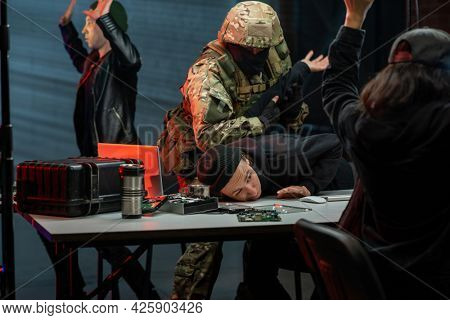 Military men in camouflage outfit capturing cyber criminals in office