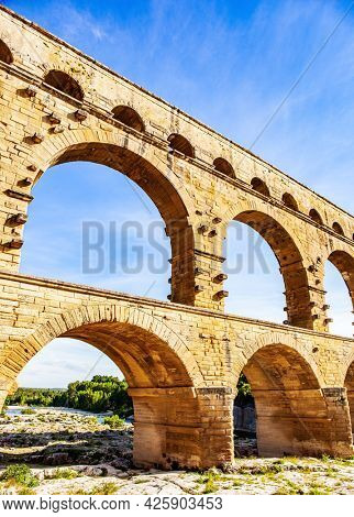 The Pont du Gard is the tallest Roman aqueduct. Thrown across the Gardon River. The aqueduct is a three-tiered arcade of yellow-pinkish limestone. A masterpiece of ancient Roman architecture