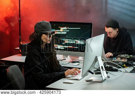 Female hacker looking at computer screen while decoding data