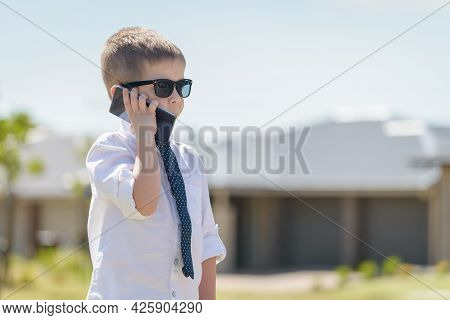 Boy Standing And Talking On The Mobile Phone While Wearing Business Attire With Sunglasses On A Brig