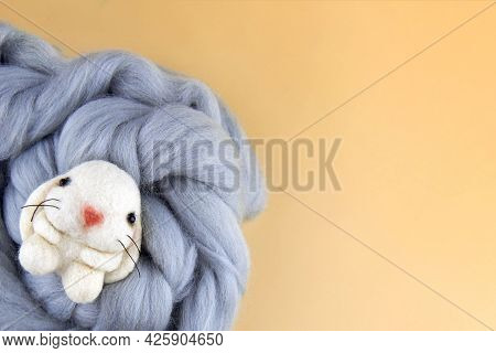 Handmade Bunny Felted Of Wool On A Beige Background, Copy Space.