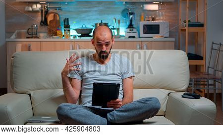 Focused Man Having Online Meeting Videocall On Tablet Computer Speaking Using Videoconference Online