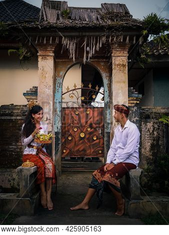 Preparation For Traditional Balinese Ceremony. Multicultural Couple Making Hindu Religious Ceremony