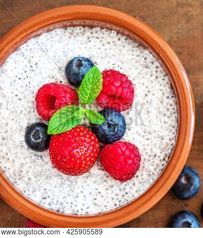 Chia Seed Pudding Made With Fruits And Fresh  Berries Over Wood Background. Chia Seeds Yogurt.