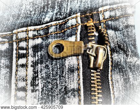 Close-up denim with seams and locks. Heavily shabby worn jeans. Metal bronze yellow lock with runner