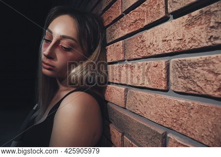 Overdosed Drug Addicted Woman Near Brick Wall. Space For Text
