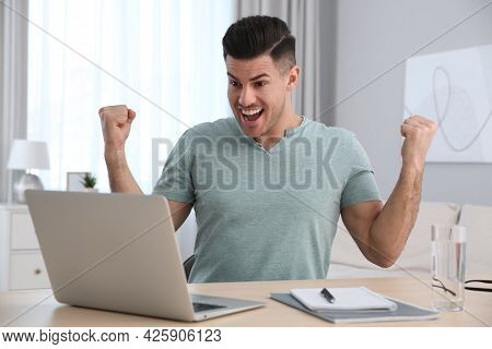 Emotional Man Participating In Online Auction Using Laptop At Home