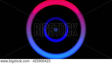 Image of multiple colourful neon circles spinning and moving on changing background. Colour light movement concept digitally generated image.