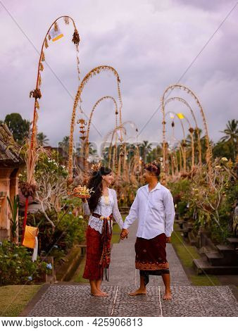 Balinese Ceremony. Multicultural Couple Going To Hindu Religious Ceremony With God's Offerings. Penj