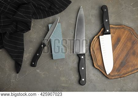 Sharpening Stone And Knives On Grey Table, Flat Lay