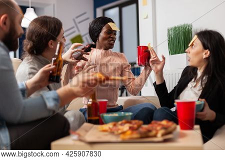 African American Woman Playing Guessing Game With Friends After Work At Office. Multi Ethnic Group O
