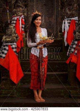 Balinese Culture And Religion. Caucasian Woman Standing Near The Temple In Bali, Holding God's Offer