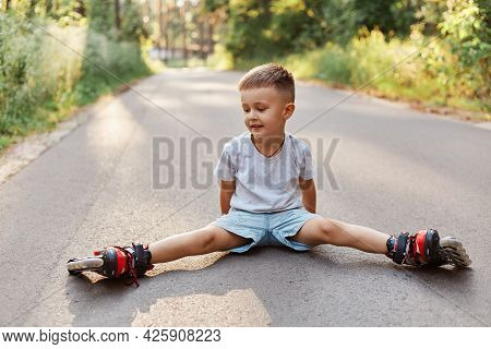 Outdoor Shot Of Happy Little Boy Sitting In Twine On Asphalt Road In Roller Skating, Looking Smiling