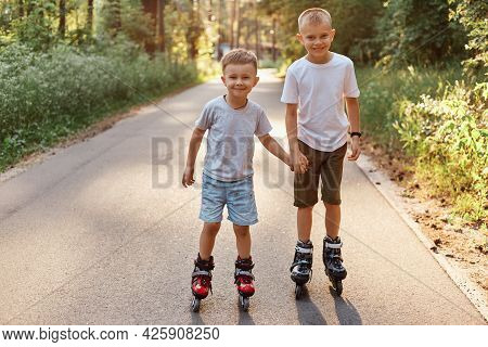 Portrait Of Two Smiling Boys Brothers Wearing Casual Styles T S-shirts And Shorts Rollerblading On B