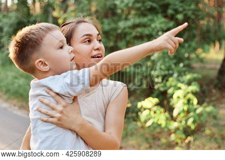 Side View Of Astonished Mother Holding Kid In Hands, Little Son Showing Mother Something Far Away, P