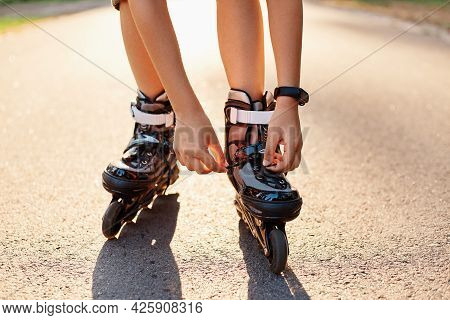 Close-up Of An Anonymous Kid's Hands Fixing Laces On Roller Blades Before Skating, Unknown Child On