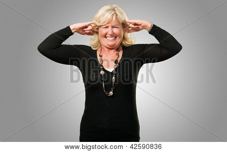 Mature Woman With Fingers In Ears against a grey background