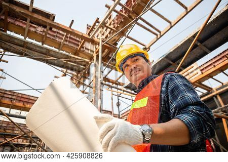 Worker Man In Hard Hat Holding Blueprint And Looking At Camera Checking And Planning Project At The