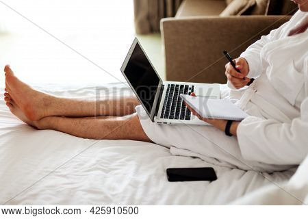 A Man With A Laptop On The Bed. The Man In The Bedroom Is Lying On A Bed With A Computer On His Lap
